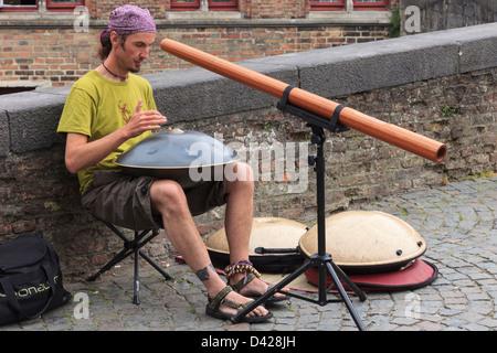 Street entertainer playing music in Bruges, East Flanders, Belgium, Europe. - Stock Photo