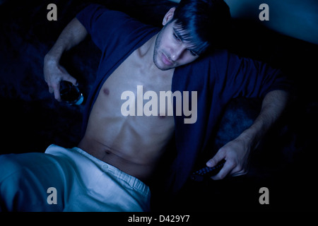 A man in his pajamas lit by the blue glow of tv, holding a remote control in one hand and a drink on the other. - Stock Photo