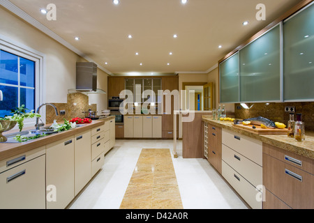 Large modern kitchen in Spanish villa with recessed ceiling lights and marble insert in white ceramic floor - Stock Photo