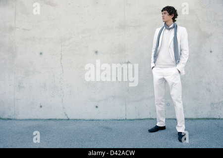 a young man wearing a fashionable light suit for spring and summer, standing on one side of a concrete wall Stock Photo