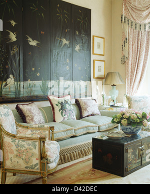 Oriental folding screen on wall above sofa in townhouse drawing room with painted oriental chest - Stock Photo