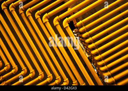 An image of yellow pipes forming an interesting pattern. - Stock Photo