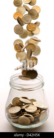 pound coins falling into a glass jar - Stock Photo