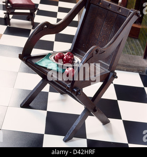 Plate of red apples on dark wood chair on black+white vinyl checkerboard floor - Stock Photo
