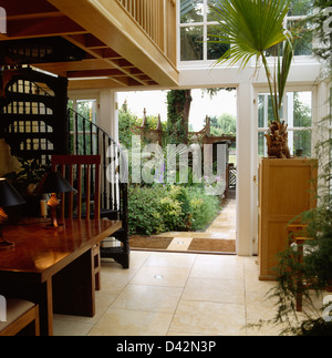Travertine tiled floor in large conservatory dining room with tall palm tree in pot beside double glass doors open - Stock Photo