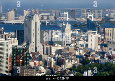 Daytime aerial view of metropolitan downtown Tokyo city skyline with high-rise buildings including Rainbow Bridge - Stock Photo