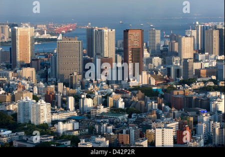 Daytime aerial view of metropolitan downtown Tokyo city skyline with high-rise buildings including Tokyo Bay - Stock Photo