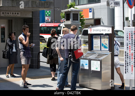 Many public outdoor spaces around Tokyo are off limits to smokers except at specially designated smoking areas. - Stock Photo
