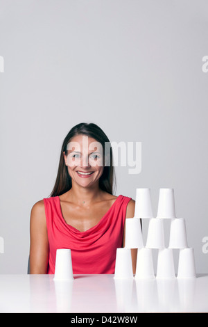 Freiburg, Germany, a young woman sits in front of a pyramid from paper cups - Stock Photo