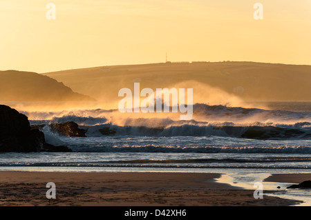 Strong winds blowing spray off incoming waves at Harlyn Bay in Cornwall. - Stock Photo