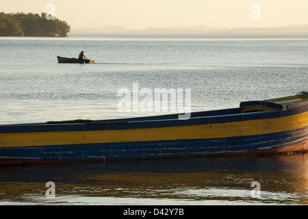 A man rows a fishing boat across lake Nicaragua in Moyogalpa on the island of Ometepe in Lake Nicaragua - Stock Photo