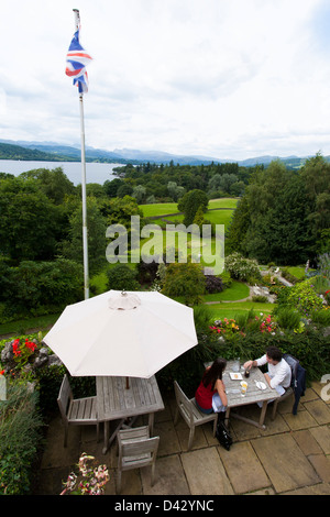 A couple have lunch on the patio of a Lake District hotel overlooking Lake Windermere. - Stock Photo
