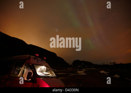 tourists on cloudy night northern lights chase aurora borealis near tromso in northern norway europe - Stock Photo