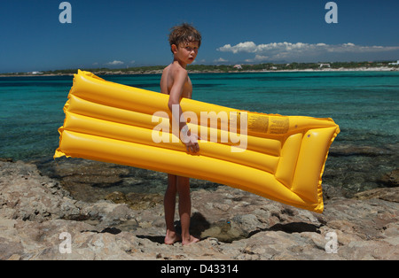 Santa Margherita di Pula, Italy, boy stands with his air mattress on the beach - Stock Photo
