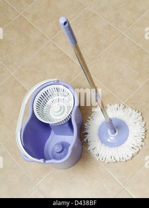 Rotary mop and empty bucket on tile floor - Stock Photo