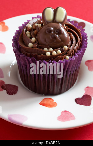 Easter chocolate cupcake with milk chocolate bunny rabbit on set on plate with hearts on - Stock Photo