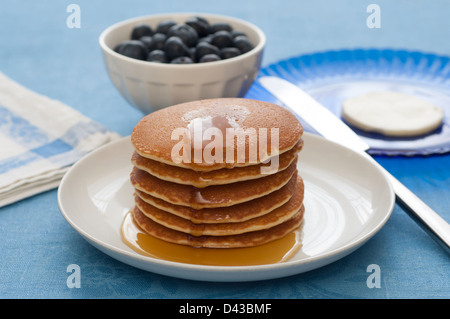 Close-up view of a stack of Pancakes with maple syrup. Butter and berries on the background. - Stock Photo