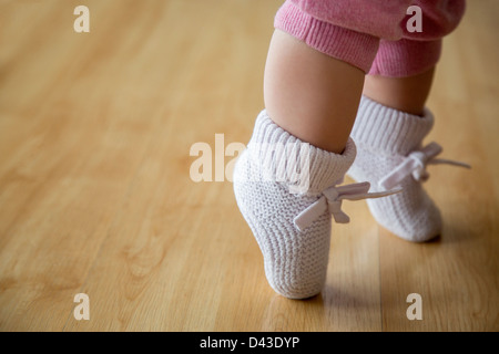 Baby girl in pink booties - Stock Photo