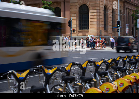 Brisbane City Council Bus in the city and pedestrians - Stock Photo