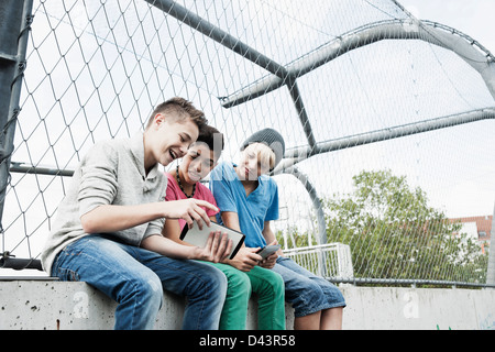 Three Boys Playing Video Games in Playground, Mannheim, Baden-Wurttemberg, Germany - Stock Photo