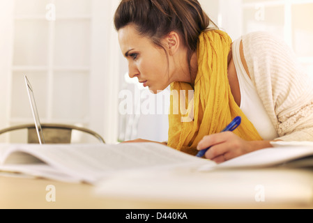 College student reading something in laptop screen and writing it down on her notes - Stock Photo