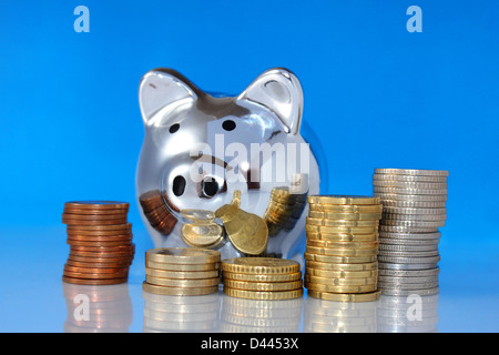 metal pig bank and piles of coins on the blue background - Stock Photo