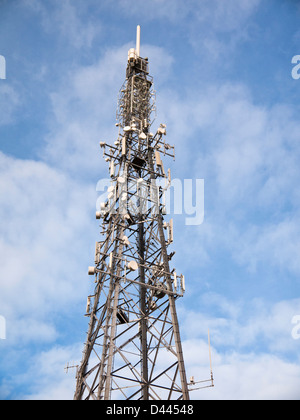 Communications tower with many aerials and dishes against a blue sky, UK - Stock Photo