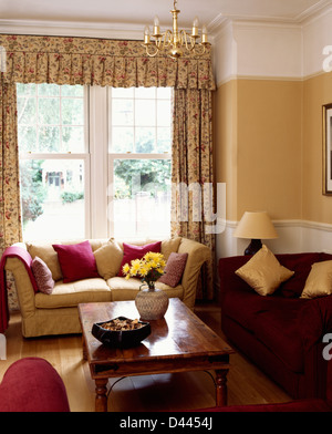 Indonesian wood coffee table and red sofa in living room with cream sofa in front of tall windows with patterned - Stock Photo