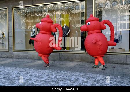 The German supermarkt chain Kaiser's Tengelmann advertises with two promoters wearing red coffee pots on Kurfürstendamm in Berlin, Germany, 12 February 2012. The red coffee pot is the logo of the company. Photo. Berliner Verlag/S.Steinach