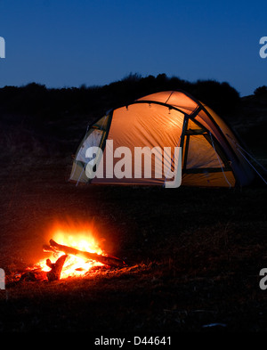 tent glows at night with campfire in front symbolizing camping holiday or vacation in the country - Stock Photo