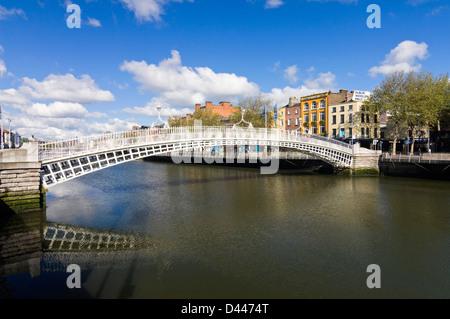 Horizontal view of the Ha'Penny Bridge aka Droichead na Leathphingine or Liffey bridge in Dublin on a sunny day. - Stock Photo