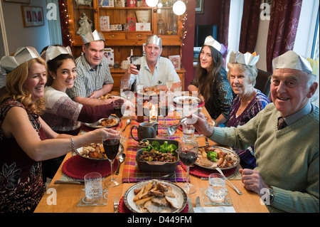 Horizontal portrait of three generations of a family enjoying Christmas lunch together round the table. - Stock Photo
