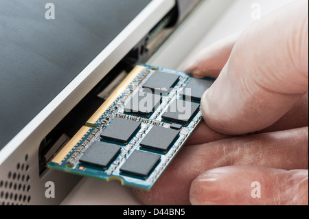 IT Technician replacing a random access memory (RAM) board in a computer. - Stock Photo