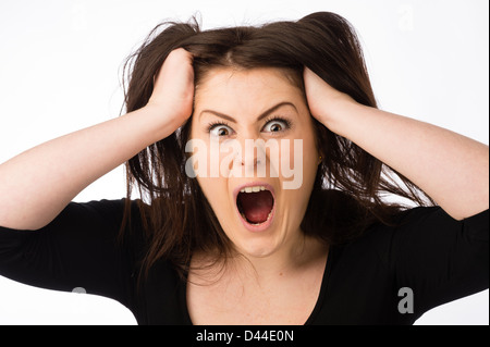 A young angry shouting woman, tearing out pulling her brown hair out , UK - Stock Photo