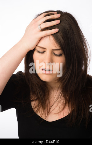 A young ill sick ailing woman, brown hair, hand on her forehead UK - Stock Photo