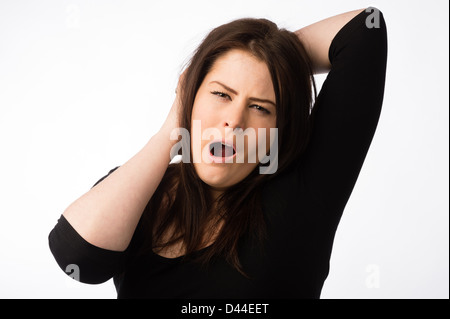 A young tired sleepy yawning woman, brown hair, UK - Stock Photo