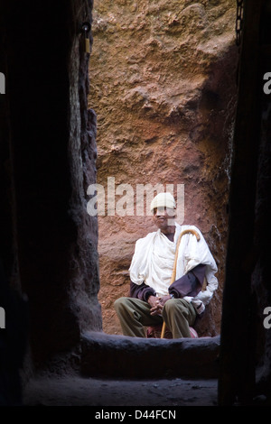 Priest inside rock hewn church Lalibela, Ethiopia Africa - Stock Photo