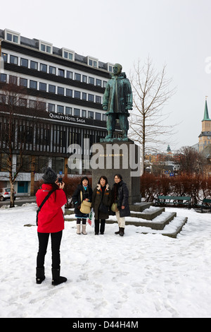 female asian tourists taking photos in front of Roald Amundsen statue in Tromso troms Norway europe - Stock Photo