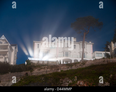 Bright sunlight reflects off windows of cliff top building, highlighting early morning mist. - Stock Photo