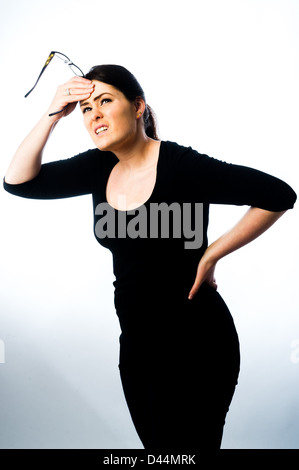 A young woman, brown hair, suffering back pain, tension stress  UK, rubbing her back and head - Stock Photo