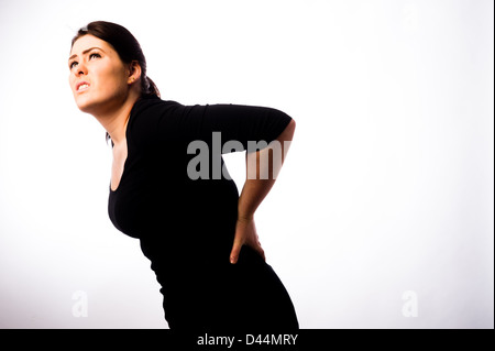 A young woman, brown hair, suffering back pain, UK - Stock Photo