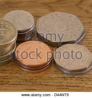 Piled coins on a table - Stock Photo