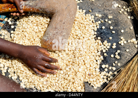 ANGOLA Kwanza Sul, rural development project, village Catchandja, girl pounding maize to flour - Stock Photo