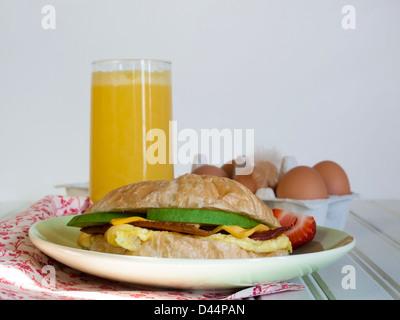 Croissant breakfast sandwich with orange juice served for breakfast. - Stock Photo
