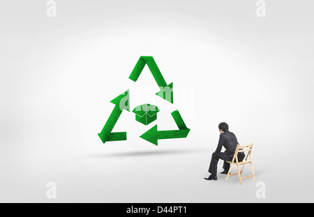 businessman looking at a green box inside recycling sign - Stock Photo