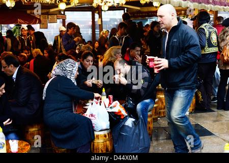 Local Turks enjoy a fish sandwich by the Galata bridge in Istanbul. - Stock Photo