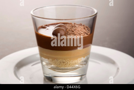 Layered chocolate dessert served in a glass on a white plate garnished with flakes of chocolate and maltesers - Stock Photo