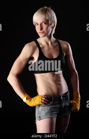 boxing young woman on black background in dramatic lighting - Stock Photo