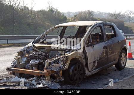 A vandalised and burned out car abandoned in a lay by beside a busy road - Stock Photo