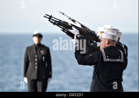 US Navy honor guard render a gun salute during a burial at sea for 20 former service members aboard the aircraft - Stock Photo